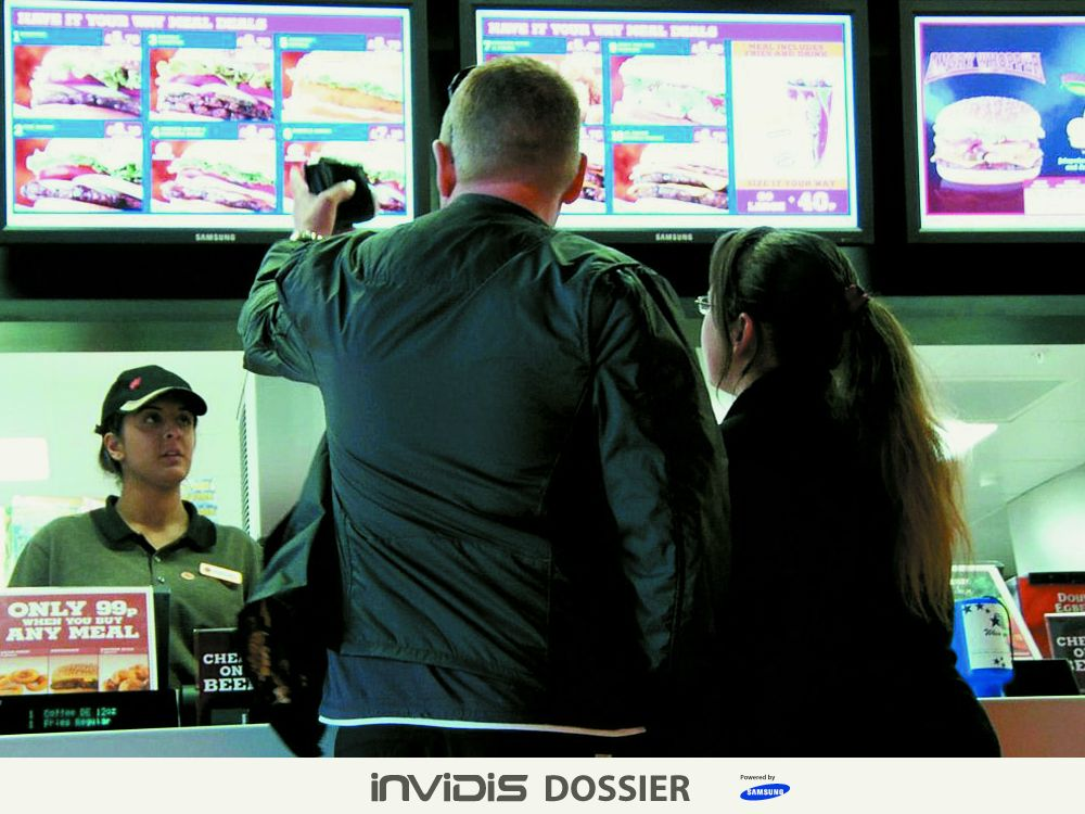 Kunden eines Quick Service Restaurants und Digital Menu Boards (Foto: Scala)