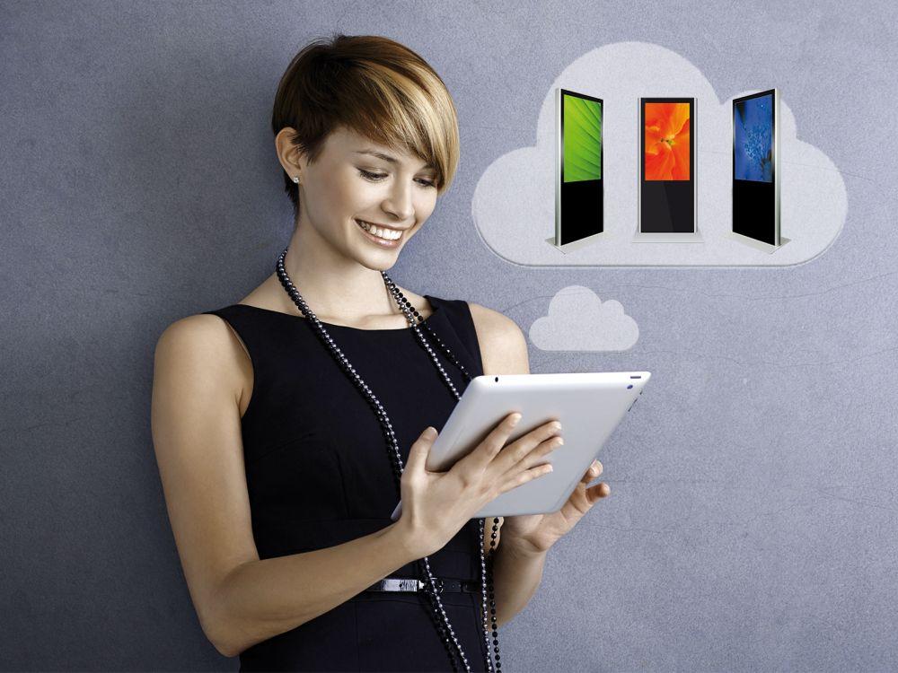 Nutzerin mit Tablet steuert DS-Installation (Foto: md Signage)