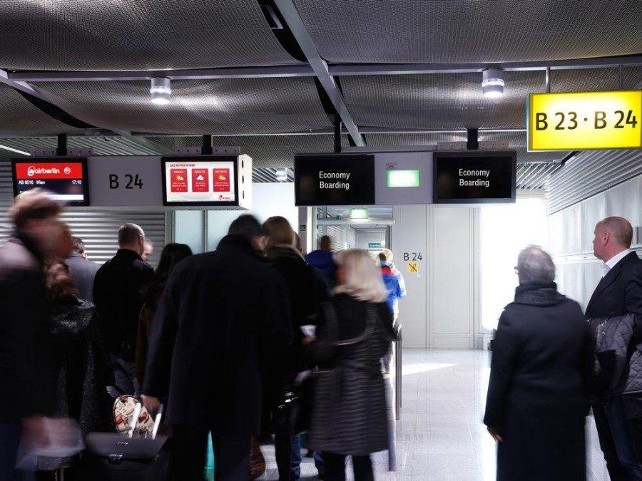 DUS Ad Gate Reisende auf dem Weg nach Wien vor den Screens (Foto: Flughafen Düsseldorf GmbH)