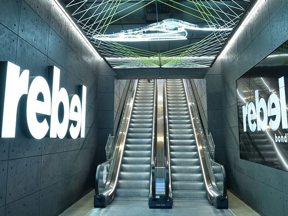 Eingang mit Rolltreppen und Signage - Rebel Flagship in Sydney (Foto: Rebel)
