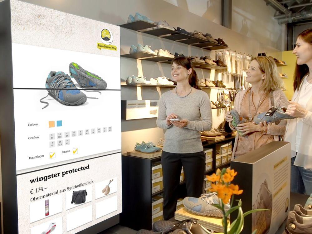 Kundinnen am PoS nutzen Guided Selling Funktionen an einer Video Wall (Foto: Bütema AG)