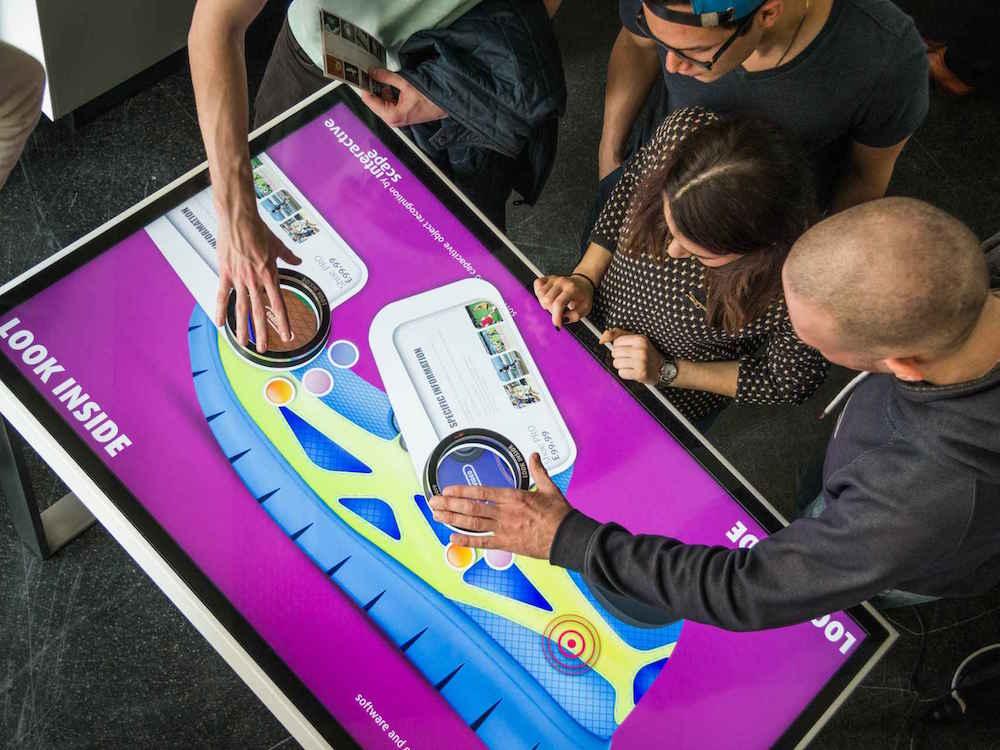 Nutzer testen Multitouch-Applikation Lupe an einem Touch Tisch (Foto: interactive scape)
