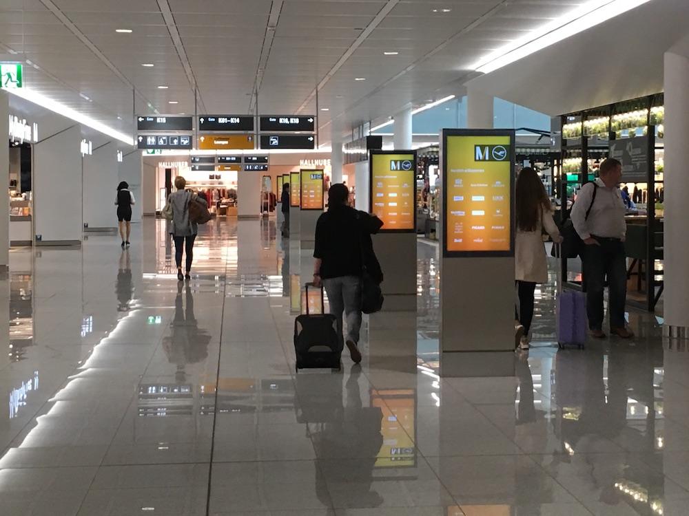 Kunden und Passagiere im Satellit T2 vor einer Reihe von DooH Screens (Foto: invidis)