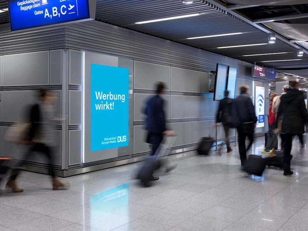 Passagiere am Airport Düsseldorf passieren Werbeträger am Gate B (Foto: Flughafen Düsseldorf / Andreas Wiese)