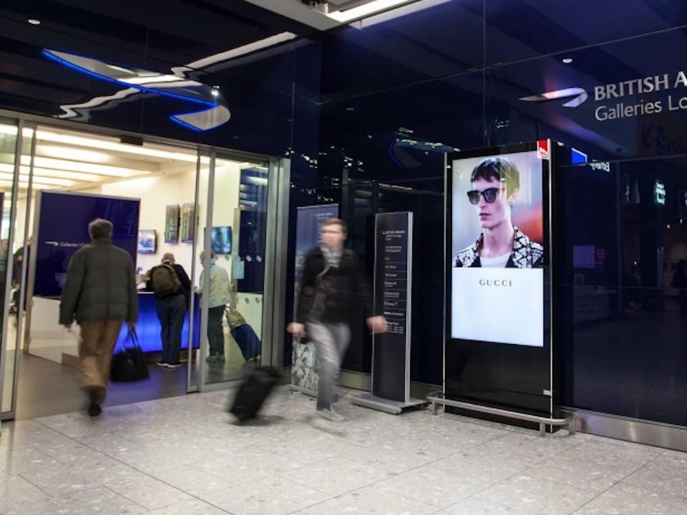 Kampagne von Gucci auf einem DooH Screen nahe der BA Business Lounge (Foto: JCDecaux)