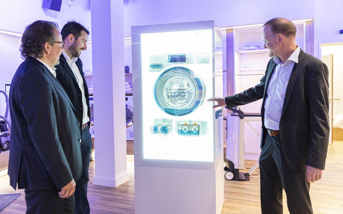 Dr. Steffen Freichel (Miele, Mitte), Stefan Holighaus und Andreas Müller (xplace, links und rechts) vor der virtuellen Waschmaschine. (Foto: xplace)