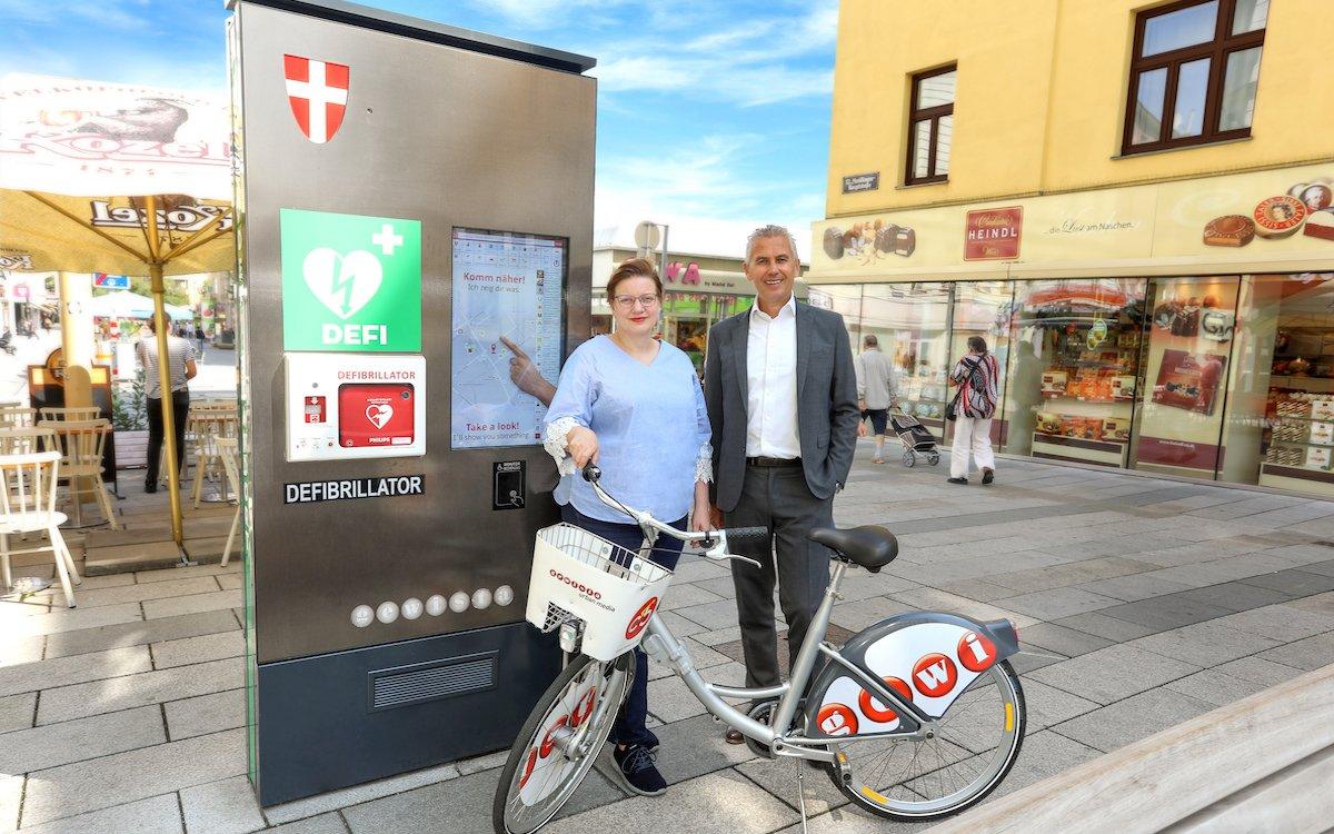 Gewista CEO Franz Solta mit der Gewista-CSR Verantwortlichen Andrea Nowak Mann vor einem digitalen City Light mit eingebautem Laien-Defibrillator und einem Citybike (Foto: Gewista / Katharina Schiffl)