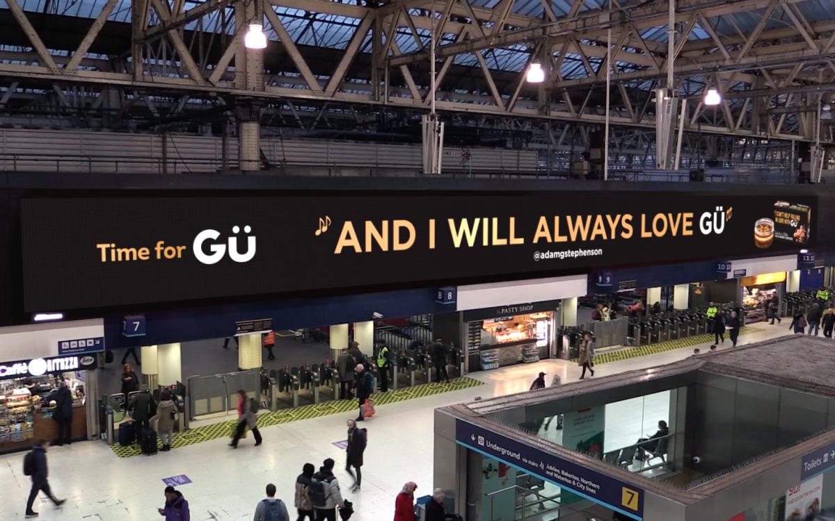 Süße Liebesbriefe mit Gü auf dem größten Indoor-Bildschirm Großbritanniens an Londons Waterloo Station (Foto: Grand Visual)