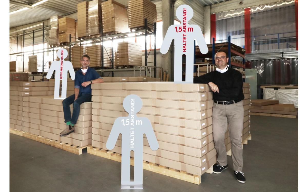 Der Kölner Digital Signage-Hersteller marketing-displays bietet jetzt auch Distancing-Figuren, die unter den vielen Corona-Plakaten und Lösungen besser auffallen sollen (Foto: marketing-displays)