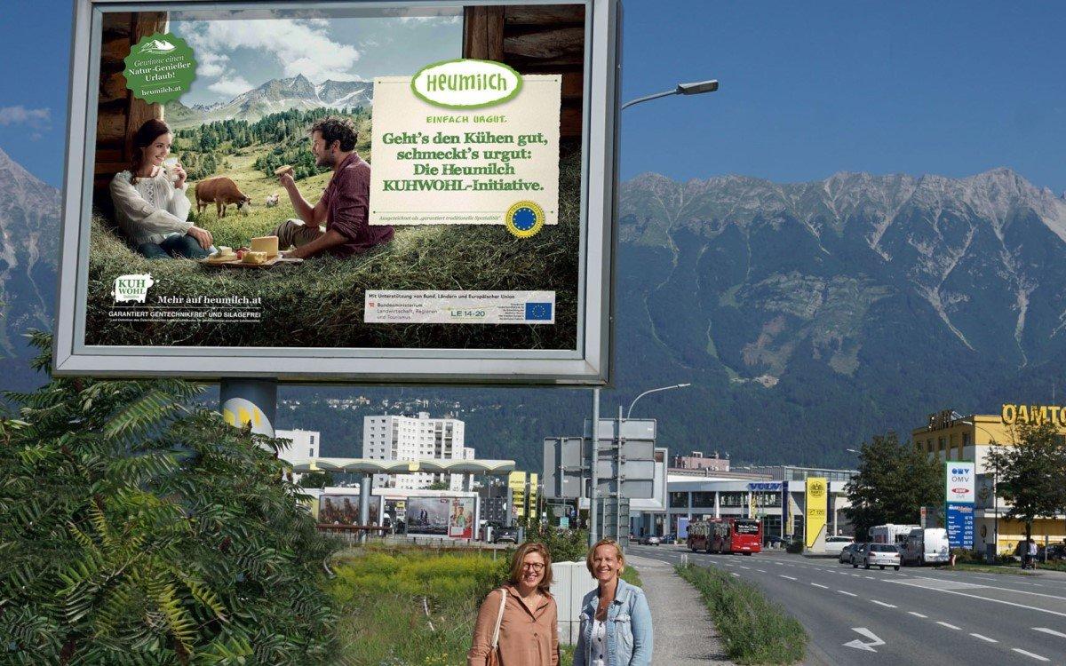 Christiane Mösl (l), Geschäftsführung ARGE Heumilch Österreich und Brigitte Huber, Account Manager Epamedia Tirol vor einem Poster der Kuhwohl-Kampagne (Foto: Epamedia)