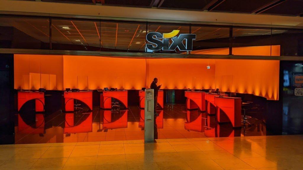 Sixt setzt auf Orange und verbannt drei Displays hinter spiegelnder Wand (Foto: invidis)
