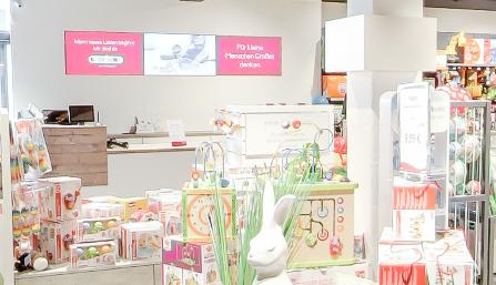 Die Screens, die Bütema in den BabyOne-Filialen installierte, befinden sich zum Beispiel hinter der Verkaufstheke. (Foto: Bütema AG)
